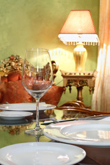 glass and white plates at table in cozy restaurant