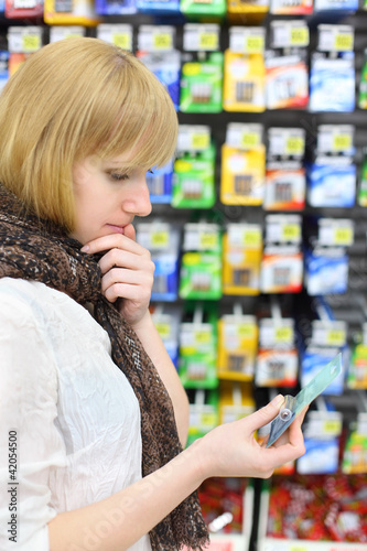 Blonde girl wearing scarf looks at battery in shop;