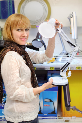 Blonde girl wearing scarf holds white table lamp in shop