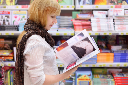 Blonde girl wearing scarf thumbs book in supermarket