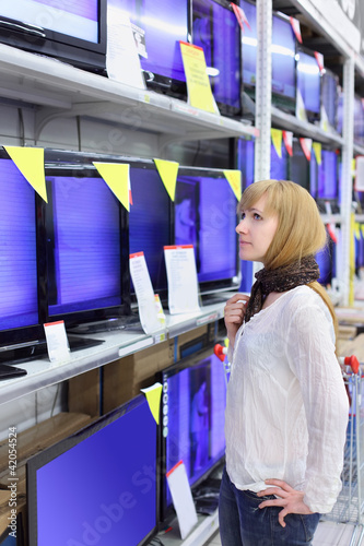 Blonde girl wearing scarf looks at plasma TVs in supermarket