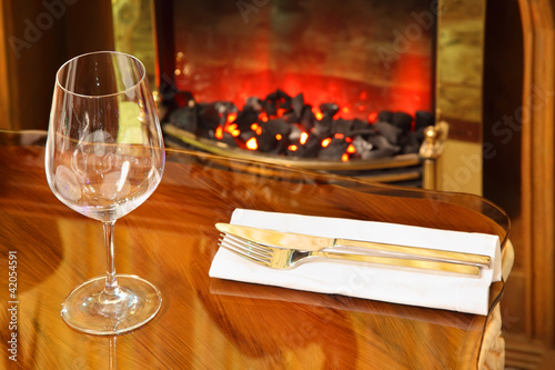 empty glass, knife and fork on napkin at table in restaurant