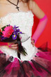 hands of beautiful bride wearing in unusual dress hold bouquet