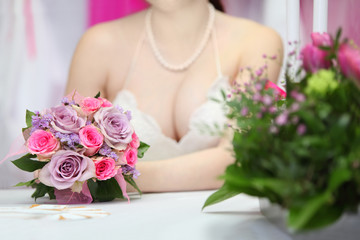 decollete of young bride, which sits at table with candles