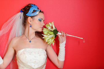 beautiful young bride with blue makeup and mask in hairdo