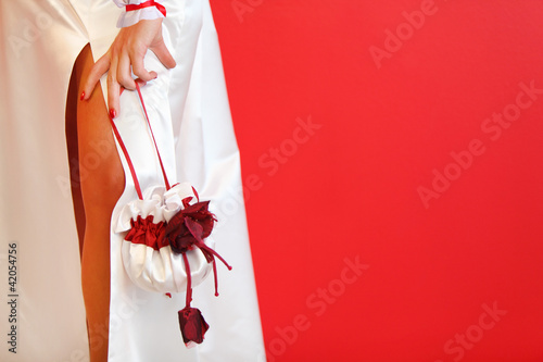 cut of white wedding dress and beautiful silk handbag on red