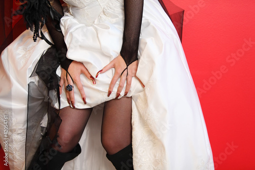 hands of bride and hem of unusual white wedding dress on red
