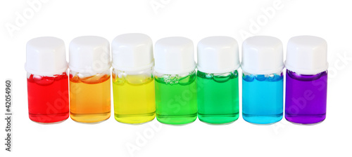 Seven small bottles of different colored aromatic oils isolated