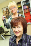 Hairdresser makes hair styling for woman by hair spray in salon