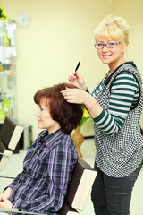 Hairdresser makes hair styling for woman by rake-comb