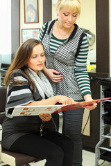 Two women look catalog of hair colors near mirror in salon