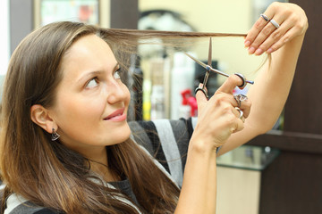 Smiling woman mows her hair with small scissors in beauty salon