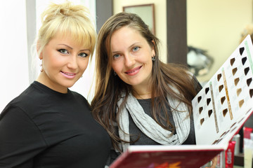 Smiling client and hairdresser with catalog of hair colors