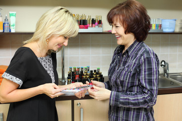 Woman shows samples for manicure nail to customer