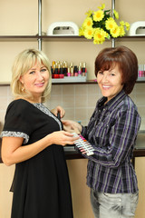 Two smiling women with samples for manicure nail in beauty salon