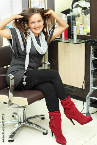 Happy woman sits in armchair and touches hair in beauty salon