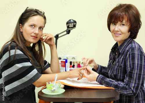 Manicurist makes manicure by nailfile for woman in beauty salon;