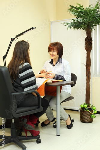 Manicurist makes manicure for woman in beauty salon
