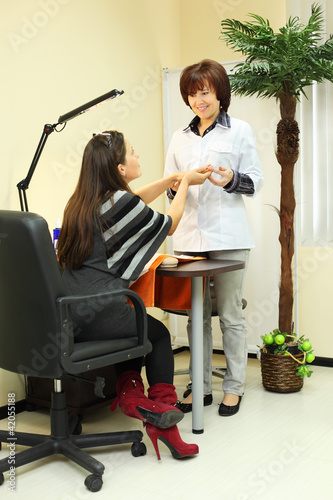 Smiling manicurist holds customer hands in beauty salon