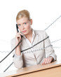 Businesswoman sitting at a desk tied with phone cable, isolated