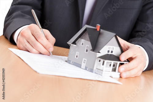 Business man signs contract behind household architectural model