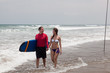 man with surf and the girl go on an ocean coast