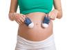 schwangere Frau hält Babyschuhe an Bauch