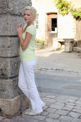 Attractive summery young woman standing on cobbled street