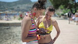 Two female friends using tablet computer on summer vacation