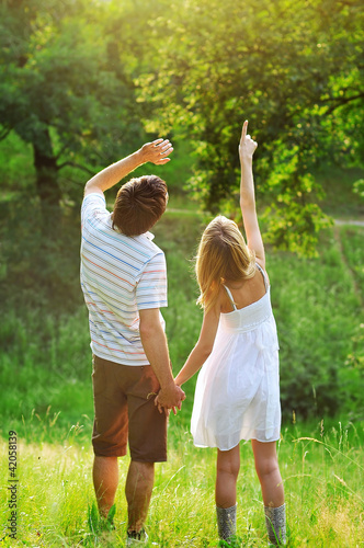 Young couple holding hands and standing on grass.point to sky