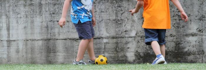 BAmbini giocano a calcio in giardino