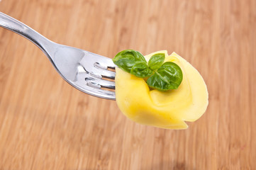 Tortellini on a fork with wooden background