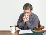Businessman at Desk Blowing Nose