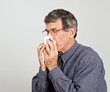 Man with Allergies, Flu or Cold Blowing His Nose
