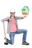 Tradeswoman holding up an energy efficiency rating chart