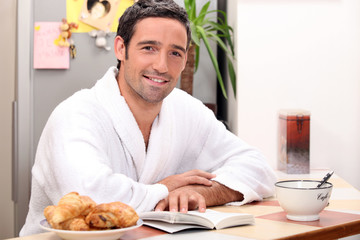 Man reading a book and eating a continental breakfast