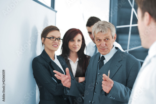 Small business team in the office in front of a board
