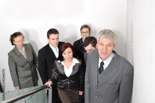 Business people ascending office stairs towards camera