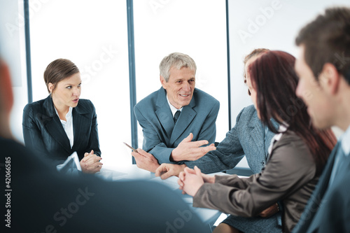 Portrait of a positive manager with his team sitting
