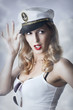 Pin-up girl in captain cap and sun glasses