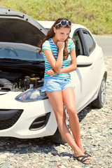 Woman is standing near broken car