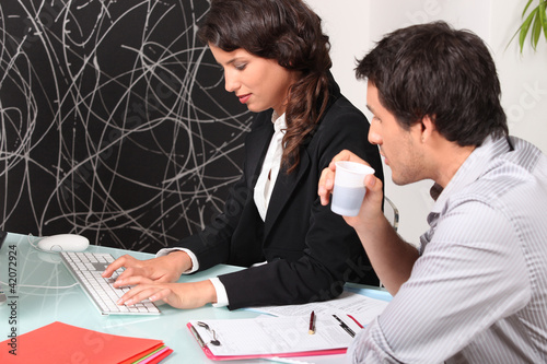 businessman and businesswoman drinking coffee in the office