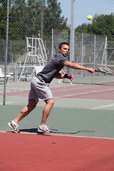 Man playing tennis on a hard court