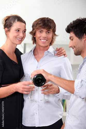 Three friends drinking champagne at new years