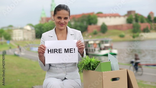 "Happy jobless businesswoman holding paper with ""HIRE ME"" sign"