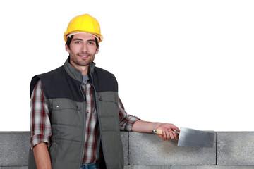A stonemason holding a trowel
