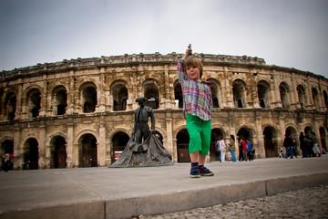 Enfant jouant devant les arènes de Nîmes