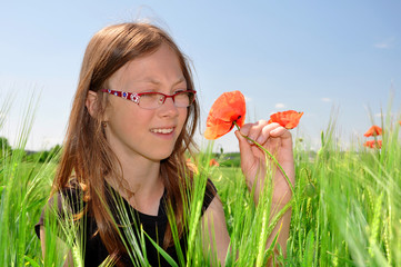 The girl in the wheat field with red poppy