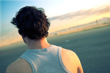 hombre de espaldas en paisaje de atardecer