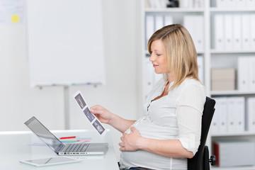 schwangere frau schaut ultraschall-fotos im büro